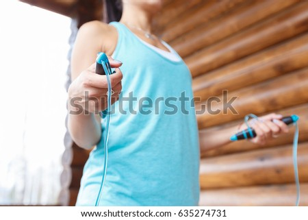 Fit young woman with jump rope in a nature. Fitness sporty female doing skipping workout outdoors on a sunny day on Wooden terrace in the country house. #635274731