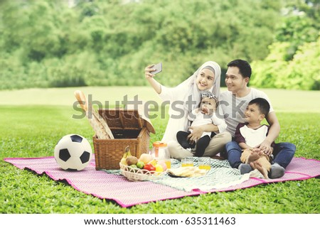 Portrait of Muslim family using a mobile phone to take a picture together while picnicking in the park