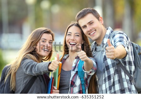 Three happy students looking at you with thumbs up in an university campus Royalty-Free Stock Photo #635351252