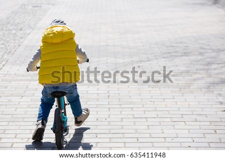 Back view on cute toddler boy riding his bike. Child on bicycle in the park. #635411948