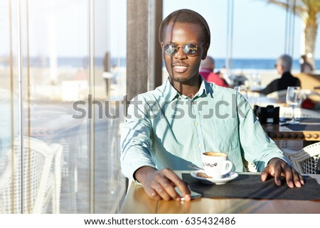 Handsome positive young Afro American man wearing mirror lens sunglasses and hat sitting alone at cafe table with mug, drinking cappuccino and looking through window, watching sun going down #635432486