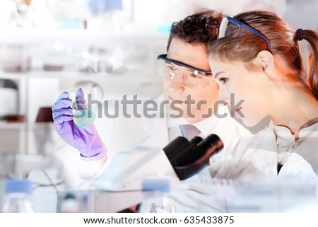 Chemical laboratory. Attractive young PhD student and her post doctoral supervisor scientist observing the blue indicator color shift after the solution  destillation. #635433875
