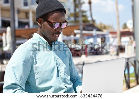 Outdoor portrait of relaxed young black male in stylish headwear and sunglasses using notebook computer, enjoying online communication with friend via video call, sitting on bench in urban setting #635434478