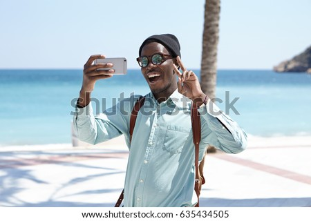 Portrait of excited happy young African American male backpacker making faces and showing peace sign to camera on cell phone while sending selfie to his friends during summer trip at seaside