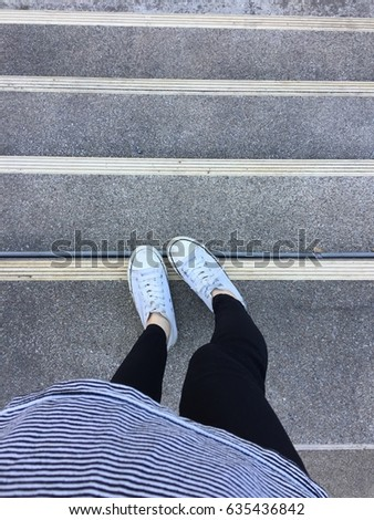 Closeup Photo of From Woman Wearing White Sneakers in The Street Great For Any Use. #635436842