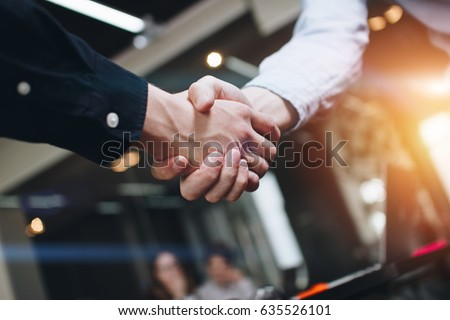 Bussines partners handshakes in modern open space on the background of coworking team on new startup project Royalty-Free Stock Photo #635526101
