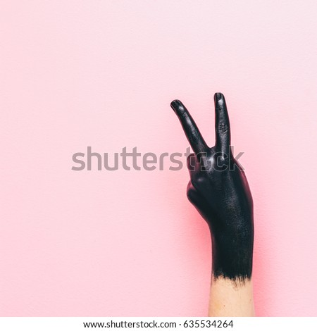 the gesture of peace, hippie black hand on pink background