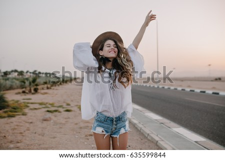 Smiling cheerful long-haired girl with curly hair breathes a full breast and enjoys freedom, standing next to road. Portrait of adorable young woman in white blouse and denim shorts having fun outside Royalty-Free Stock Photo #635599844
