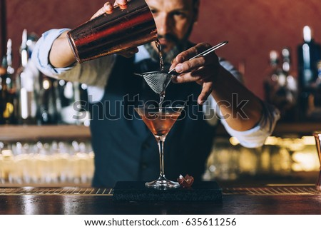 Expert barman is making cocktail at night club. #635611256