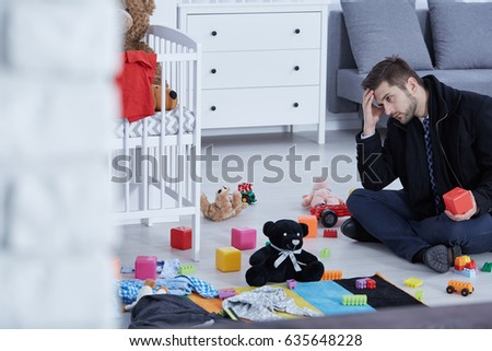 Tired young dad sitting on a floor full of children toys #635648228