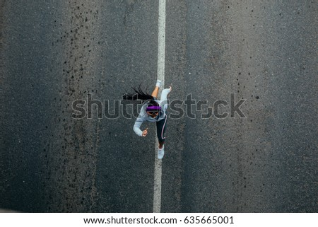 Photo from above of an athlete woman running while listening to the music on the road.