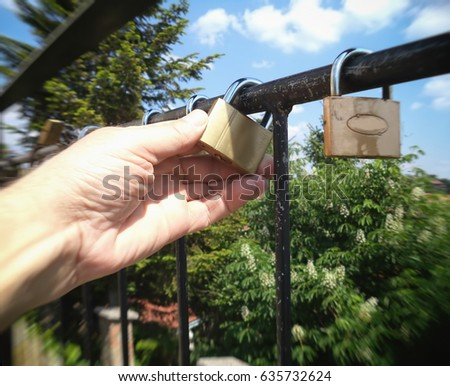 Locked love, a man looks at a padlock, background, texture, blurred image                                #635732624