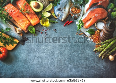 Assortment of fresh fish with aromatic herbs, spices and vegetables. Balanced diet or cooking concept Royalty-Free Stock Photo #635863769