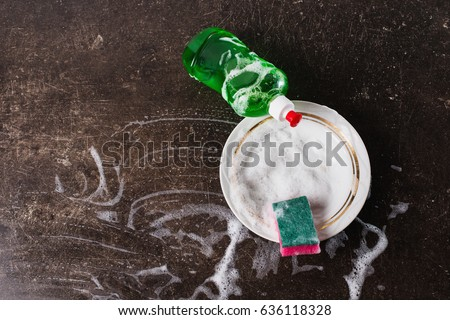White dish, detergent and sponge for dishes on a dark marble background. Hygiene. Wash the dishes Royalty-Free Stock Photo #636118328