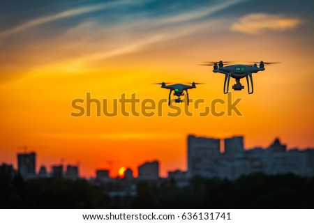Two drone quad copters with high resolution digital camera flying aerial over spectacular sunset orange sky. Cityscape silhouette with sun goes down in the background.Vehicle at sundown and copy space #636131741