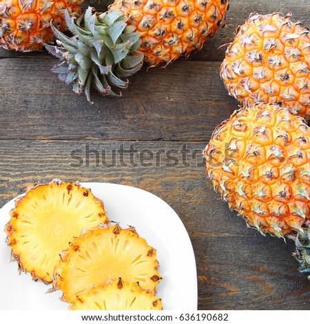 Pineapples on the old wooden texture background. Ripe tropical whole and sliced fruit on rustic wood table. Minimalistic still life of food objects on rough boards.Top View #636190682