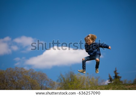 Portrait of cute happy kid boy jumping high. Child having fun and enjoying sun in the park. Lifestyle.  #636257090