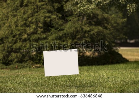 Blank white yard sign on a green lawn with a shallow depth of field