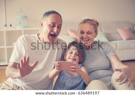 Grandmother and grandfather with their granddaughter making self-picture together. #636489197
