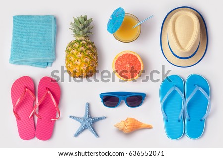 Tropical summer vacation concept with pineapple, juice and flip flops organized on white background. View from above. Flat lay Royalty-Free Stock Photo #636552071