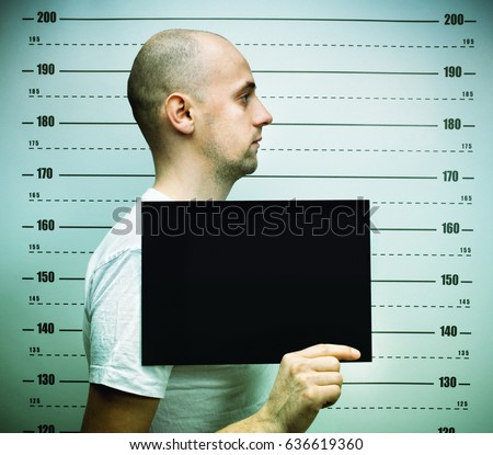 young balded man arrested and standing for police photo