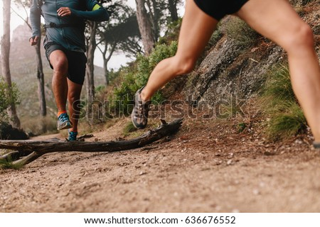 Healthy young couple running on mountain trail in morning. Young man and woman jogging on country path, focus on legs. #636676552