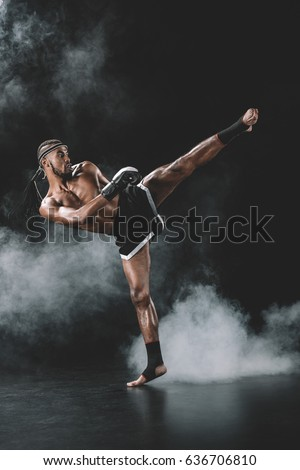 side view of concentrated muay thai fighter practicing kick isolated on black, fight club concept Royalty-Free Stock Photo #636706810