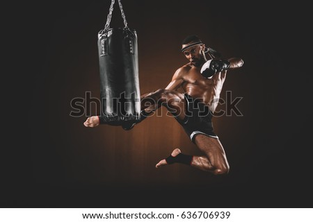 side view of focused muay thai fighter practicing kick on punching bag, action sport concept Royalty-Free Stock Photo #636706939