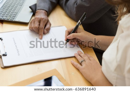 woman's hand hold ballpoint pen writing on  agreement paper sheet, fill in document template, applying for mortgage loan #636891640