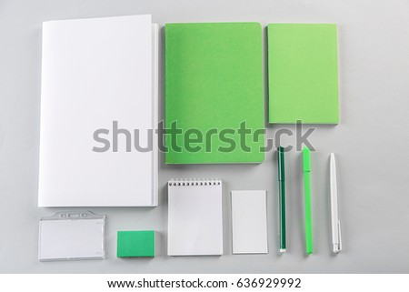 Flat lay of blank green and white goods on table #636929992