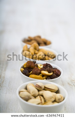 Nuts in a plate on a  wooden table. Different kinds of tasty and healthy nuts. #636967411