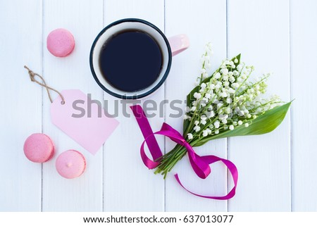 Flat lay. Mug with coffee and bouquet of lilies of the valley on a white wooden background #637013077