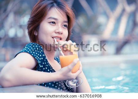 Young woman with cocktail in swimming pool #637016908