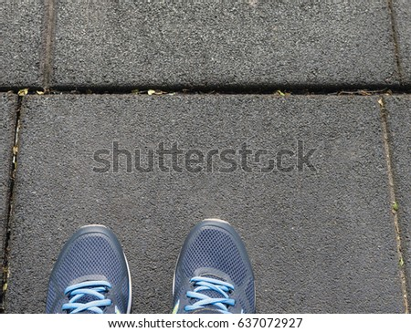 A person's feet in sports shoes on pavement. Cropped image. #637072927