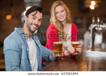 Portrait of young man and woman holding beer glasses at pub #637081894