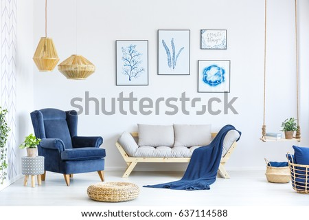 White and blue living room with sofa, armchair, lamp, posters #637114588
