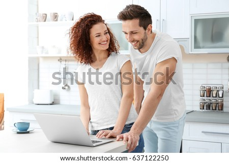 Happy young couple with laptop in kitchen #637122250