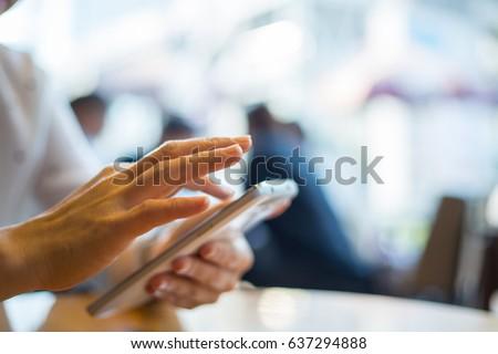 Asian woman playing smarphone in coffee shop. #637294888