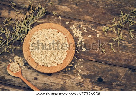 Organic oat flakes on a wooden plate. Vintage filtered and toned. #637326958