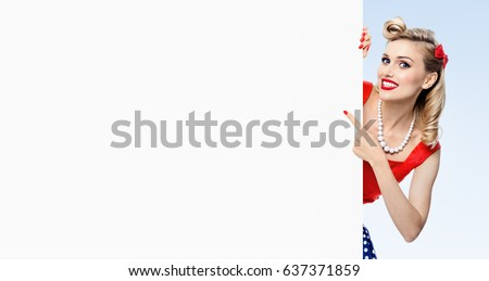 Happy smiling woman in pin-up style dress, showing blank signboard with copyspace, on blue background. Caucasian blond model posing in retro fashion and vintage concept studio shoot.