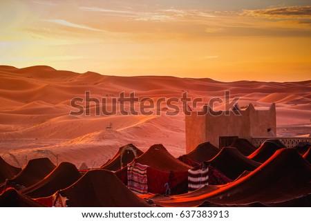 Village in the desert. Nomads in Marocco. desert.Tent houses in desert. Rising Sun in the morning #637383913
