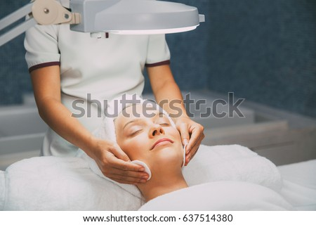Woman having cleaning facial treatment in spa #637514380