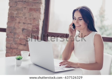 Smiling charming young business lady is talking on the phone at the cafe while checking her mail on laptop. She is wearing white stylish outfit #637526329