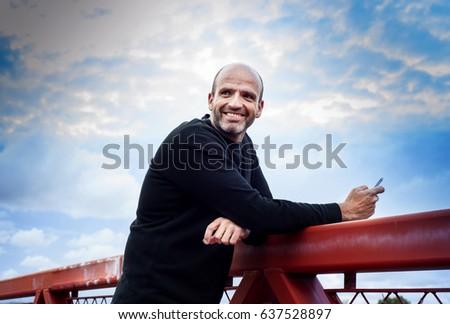 Man with phone on a bridge #637528897