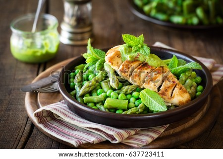 Grilled chicken breast garnished with green peas, asparagus stalks and mint sauce against dark rustic background. Healthy homemade dinner #637723411