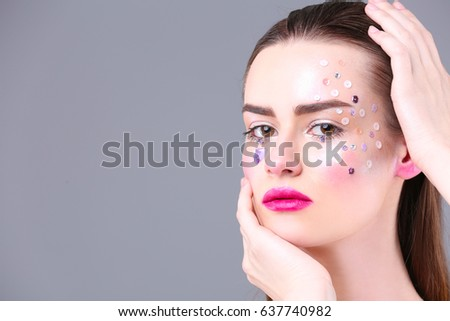 Beautiful young woman with creative make up on gray background #637740982
