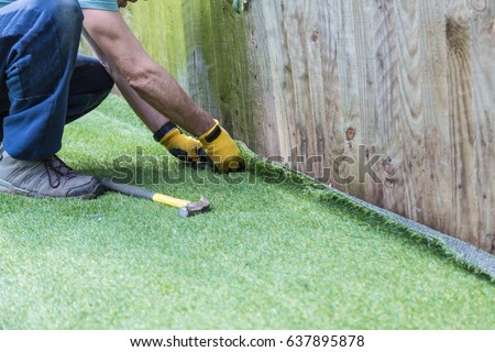 Artificial grass being installed. It has been cut to size and rolled out and laid and is being nailed down along a fence. The installer has a hammer and nails. #637895878