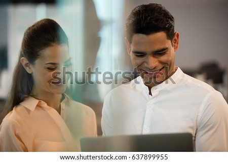 Smiling business people using laptop in office #637899955