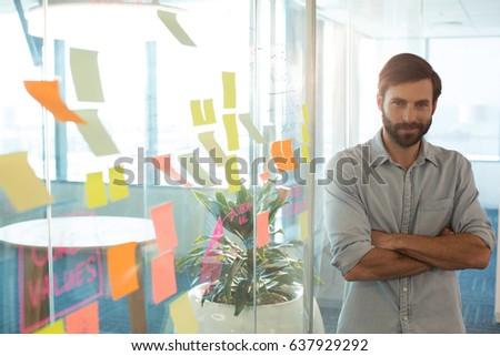 Portrait of confident businessman with arms crossed standing by strategy on glass at office #637929292