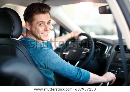 Happy young male driver behind the wheel. The guy in the car. Lifestyle scene in the car dealership Royalty-Free Stock Photo #637957153